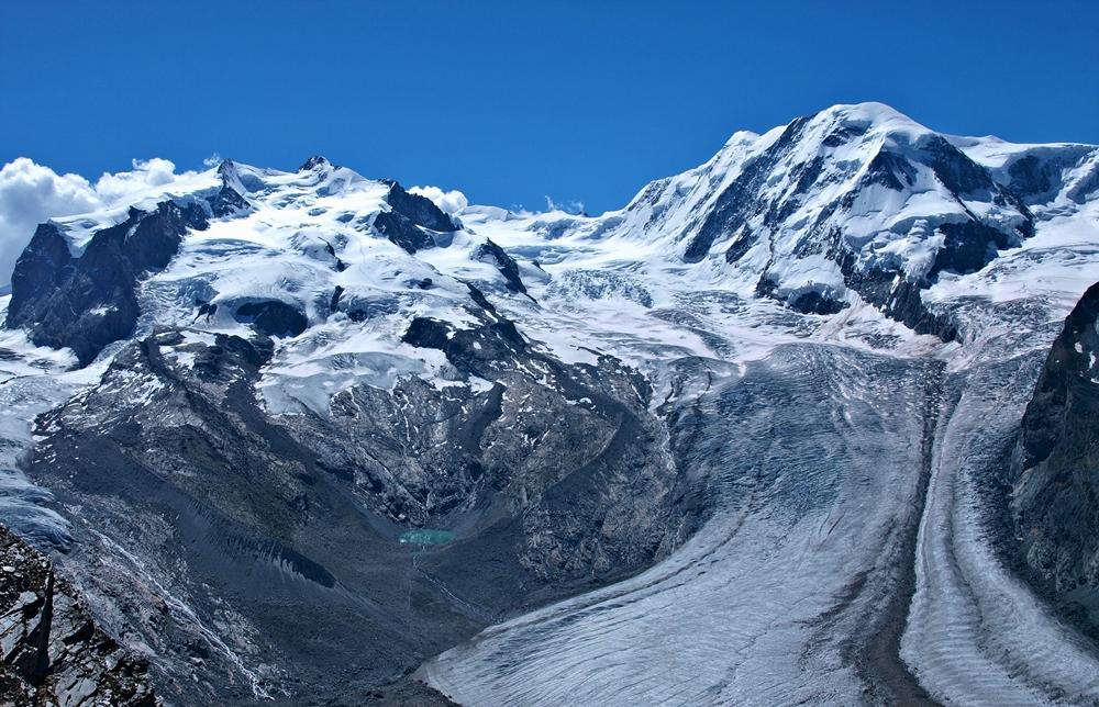 Vpravo: Dufourspitze, najvyššia hora Švajčiarska a druhá najvyššia hora Álp. Vľavo Liskamm, štvrtá najvyššia hora Álp. Medzi nimi vidieť začiatok druhého najväčšieho ľadovcového systému v Alpách – Gornerský ľadovec. Fotené začiatkom leta, keď sa snehy na vrcholkoch hôr topia.